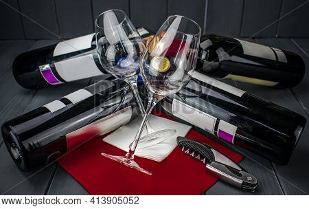 Two Bright Wine Glasses Lying On Several Bottles Of Red Wine And A Corkscrew, On Red Tablecloth, In