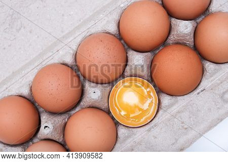 A Brown Chicken Egg With Yellow Yolk Is Half Broken Among Other Eggs In A Carton Tray
