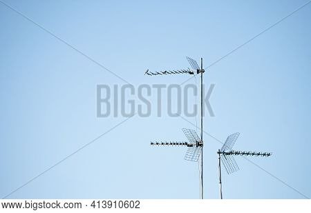 Three Television Antennas For Analog And Digital Terrestrial Television Installed On Mast On A Roof