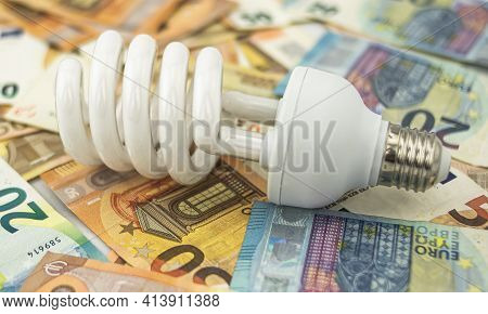Metaphor About The Excessive Cost Of Light, Energy And Electricity, Using A White Halogen Bulb On A