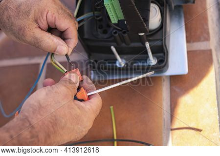 Hands Of A Man Who Are Connecting A Cable To An Electric Power Strip Of A Motor And With A Screwdriv
