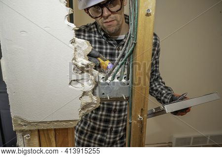 Electrician Inspecting An Electrical Outlet Between Framing Studs Where The Drywall Is Removed For H