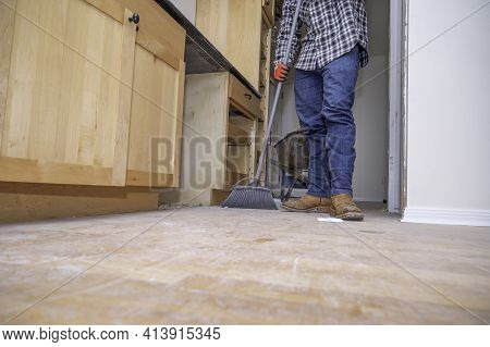 Contractor Sweeping Kitchen Floor With Broom During Home Remodeling Project