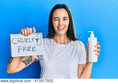Young hispanic woman holding cruelty free cosmetics winking looking at the camera with sexy expression, cheerful and happy face.