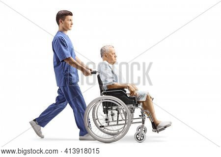 Full length profile shot of a young male nurse pushing a patient in a wheelchair isolated on white background