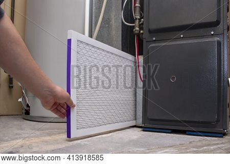 A Person Changing An Clean Air Filter On A High Efficiency Furnace