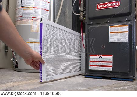 Calgary, Alberta, Canada. March 23, 2021. A Person Changing An Clean Air Filtrete 3m Filter On A Goo