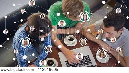 Network of profile icons against group of students using laptop at cafe. social media networking technology concept