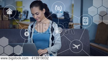 Network of digital icons against caucasian woman using computer at office. global business and networking technology concept