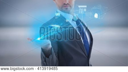 Composition of network of digital icons and data processing over hand of businessman. global technology and digital interface concept digitally generated image.