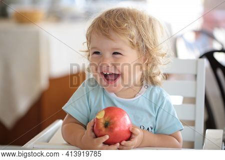 Laughing Cute Child Eating Apple. Cute Baby Eat Apples. Portrait Of Cute Smiling Laughing Caucasian