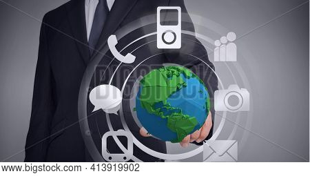 Composition of network of digital icons with globe over hand of businessman. global technology and digital interface concept digitally generated image.