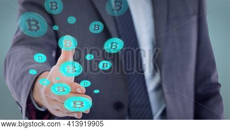 Composition of network of digital bitcoin icons over hand of businessman. global technology and digital interface concept digitally generated image.