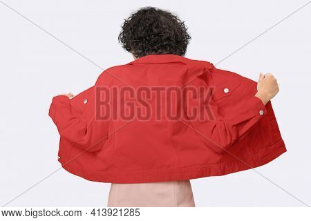 Stylish woman in red denim jacket for apparel shoot rear view