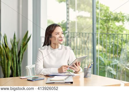 Young Asian Woman Using Smartphone While Sitting At Her Office Desk In Modern Office.