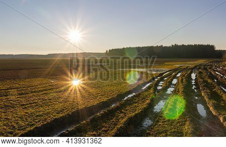 Czech Rural Agriculture Landscape. Field With Dirt Tractor Groove, Forest And Sunset Reflection In P