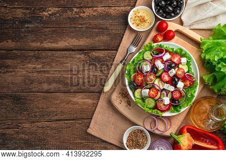Greek Salad And Ingredients On A Brown Wooden Background. The Concept Of Healthy Food.