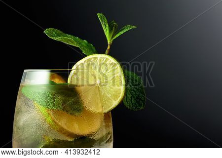 Cold Refreshing Drink With Lime Slices And Mint. Frozen Glass With A Mojito On A Black Background.