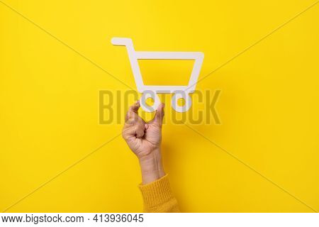 Shopping Cart Symbol In Hand Over Yellow Background
