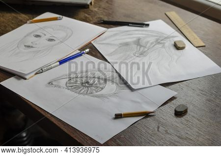 Drawings Made By A Pencil Lie On A Brown Wooden Table. Horse, Human Eye And Conceptual Female Portra