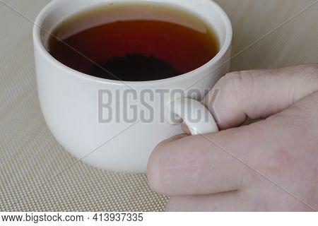 Male Hand And A Mug With Tea On A Beige Surface. White Ceramic Mug Full Of Black Tea. The Brewed Tea