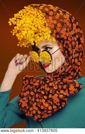 Close-up portrait of a high fashion woman posing with mimosa flowers on her head and glasses. Bright saturated colors. Pin-up style.