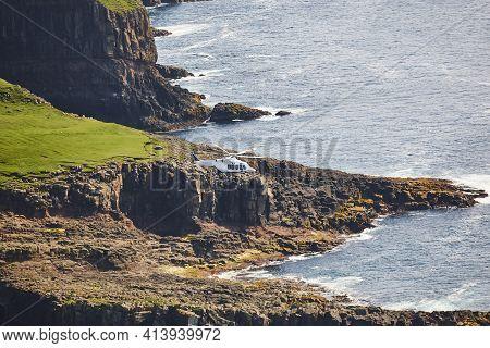 Helicopter Flying Over Mykines Atlantic Cliffs In Faroe Archipelago. Denmark