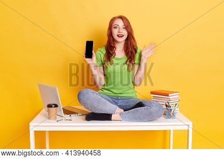 Young European Woman Showing Smart Phone Sitting On Table With Crossed Legs, Wearing Green T Shirt A