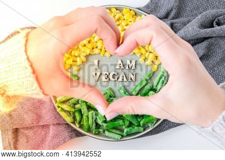 Female Hands In Shape Of Heart Love I Am Vegan Text In Plate. Veganism, Vegetarian Healthy Lifestyle