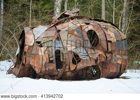 Vilnius, Lithuania - March 19 2021: Creepy Man Face In A Wood Lying On The Snow, Rusted Iron Sculptu