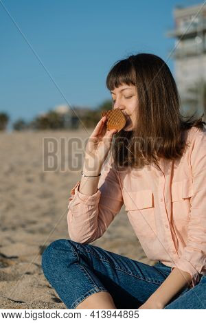 Woman Seating On The Beach At The Sunset And Sniffing Handmade Wooden Comb. Relaxing And Care Concep