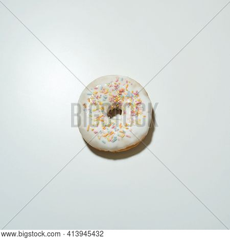 Top View Of A Freshly Baked Delicious Donut With Colorful Sprinkles And White Sugar Glaze Isolated O