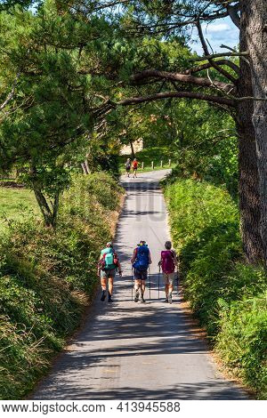 Three Friends Walking With Backpacks Trail Pilgrimage Way Of St James. Adventure, Travel, Tourism, A