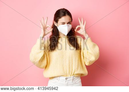 Covid-19, Lockdown And Pandemic Concept. Young Smiling Girl Assure You, Winking And Showing Okay Sig