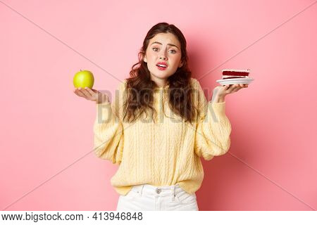 Indecisive Sad Young Woman Shrugging Shoulders, Holding Green Healthy Apple And Junk Food Piece Of C