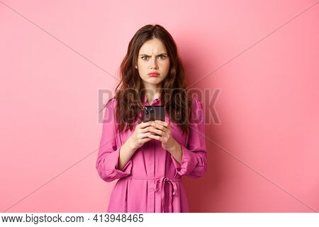 Angry Woman Frowning And Looking Confused After Reading Mobile Phone News, Standing Puzzled And Upse