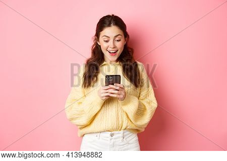 Portrait Of Excited Brunette Woman Gasping Amazed, Reading Message On Smartphone, Look Surprised At
