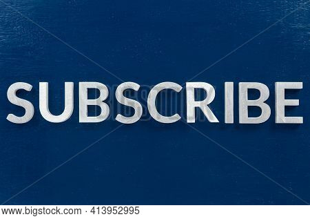 The Word Subscribe Laid With Aluminium Letters On Blue Paint Board Background