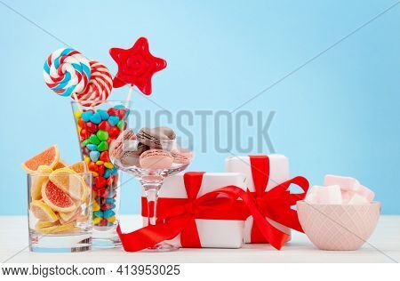 Various sweets assortment. Candy, bonbon, chocolate and macaroons in cocktail glasses and gift boxes over blue background. With copy space
