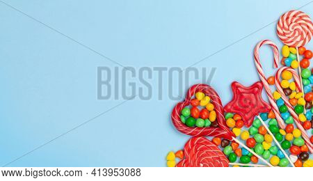 Various sweets assortment. Candy, bonbon and lollipops on blue background. Top view flat lay with copy space