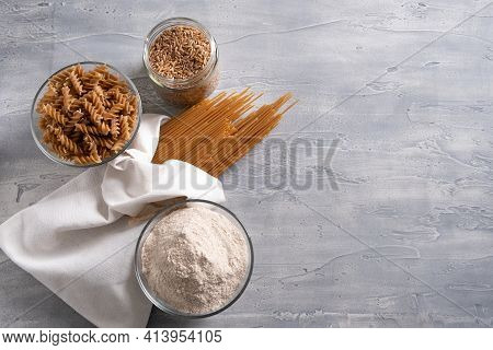 Spelt Pasta, Spelt Grain And Whole Grain Spelt Flour In Bowl And Jar.
