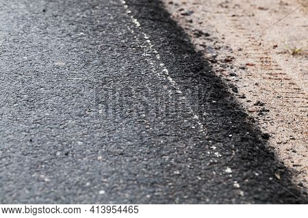 Asphalt Road Border And Sandy Roadside. Abstract Transportation Background Photo With Selective Soft
