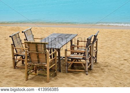 Wooden Bamboo Furniture, Table And Five Chairs Around On Sand Beach With Blue Sea Water Background I