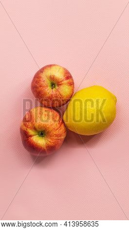 In The Vertical Photo, In The Center On A Pink Background, There Are Two Ripe Gala Apples And One Le