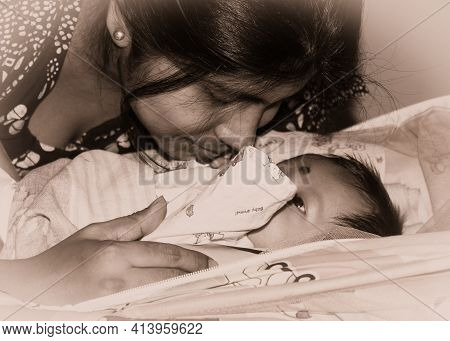Cute Newborn Baby Boy Kissed By Mother In Her Mother Lap Lying On Bed. Close Up. One Month Old Sweet