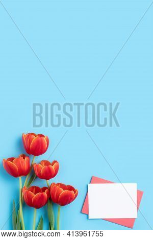 Design Concept Of Mother's Day Holiday Greeting Gift With Red Tulip Bouquet On Bright Blue Table Bac