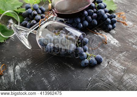 Wine Glasses Full Of Grapes On Black Stone Table. Grape Bunches With Leaves And Vines On Dark Rustic