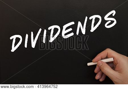 Male Hand Writes In Chalk The Words Dividends On A Black Board. Business Concept.