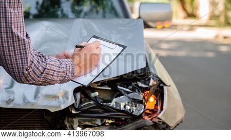 Male Insurance Agent Hands With Blank Against Destroyed Car In Car Crash Traffic Accident On Road. S