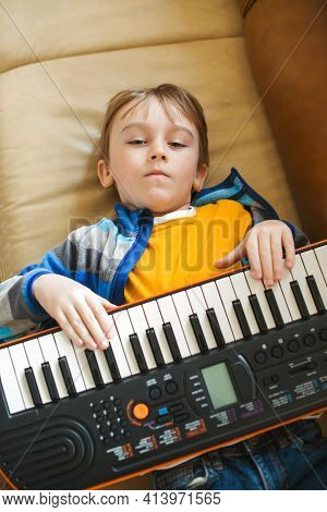 Boy Tired Of Learning To Play The Synthesizer. Little Dreamer Want To Be A Musician.